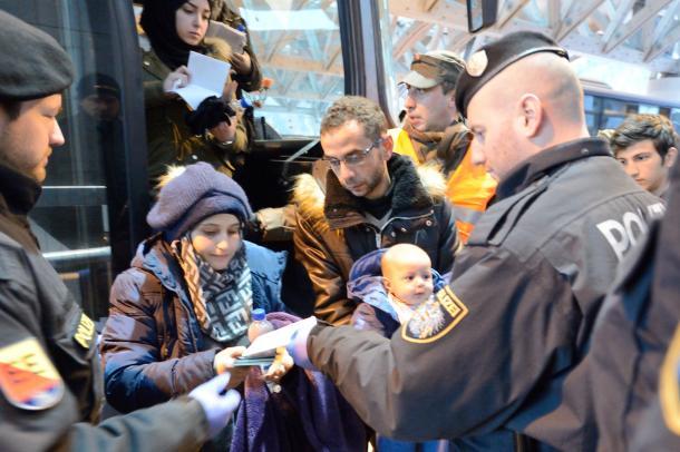 写真・図版 : バスから降りて書類のチェックを受ける若い夫婦。赤ちゃんを抱いていた=2016年1月14日、オーストリア南部カラワンケン・トンネル、喜田尚撮影