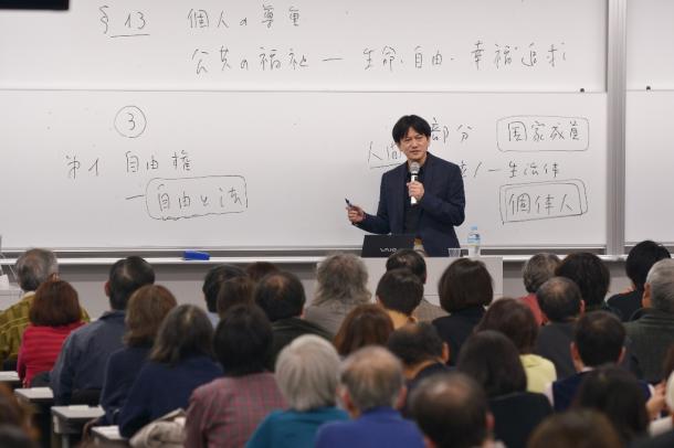 講演する石川健治さん。会場となった早稲田大学の教室には大勢の聴衆が詰めかけた