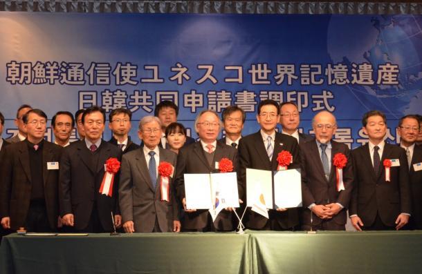 同申請書への調印を終え、記念撮影をする日韓の関係者=1月29日、長崎県対馬市