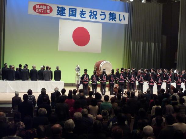 日の丸に向かい、君が代を斉唱する建国を祝う集いの参加者たち=2011年、広島国際会議場