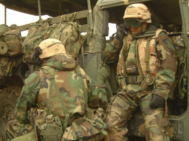 イラク軍から移動中に突然襲撃を受け、無線で近隣の部隊の状況を確認する米海兵隊員=2003年4月、イラク中部ナーシリヤ