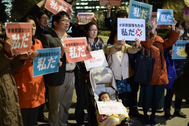 国会議事堂前での抗議行動で「保育園落ちたの私だ」と書かれた紙を持つ人たち。男児の上には「落とされたのオレだ!」の文字も=3月4日、東京都千代田区