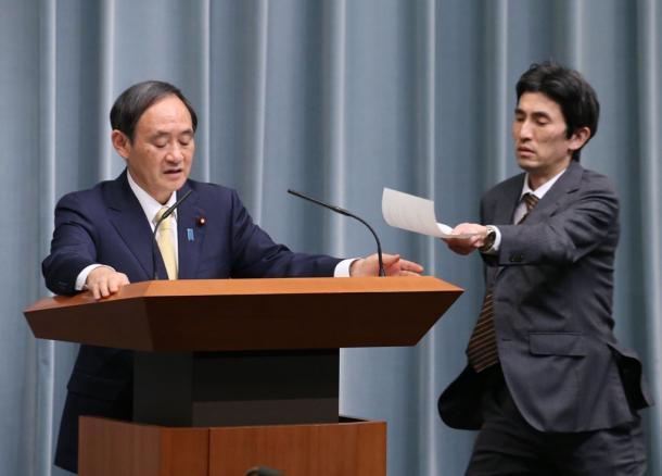 写真・図版 : 安田純平さんに関する質疑の途中、参事官(右)からメモを差し入れられる菅義偉官房長官=2016年3月17日
