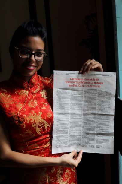 写真・図版 : 中華料理店の女性が持つ新聞には、オバマ来訪によるバスの経路変更の案内が出ている=撮影・筆者