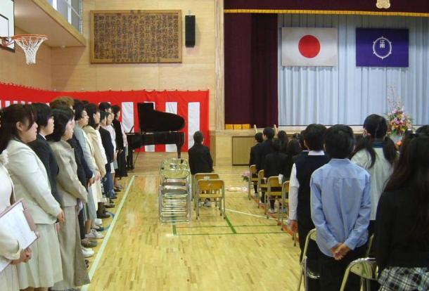 区立小学校の入学式で、起立して君が代を斉唱する教職員ら=6日、東京都江東区