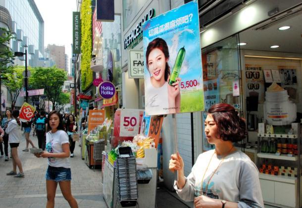 中国語で書かれたプラカードを持ち、中国人観光客らを呼び込む化粧品店の店員(右)=4月26日、ソウル・明洞