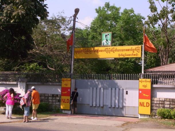 写真・図版 : 門にアウンサン将軍の肖像画を掲げたスーチーさんの自宅をのぞく観光客=ヤンゴンで 撮影・筆者