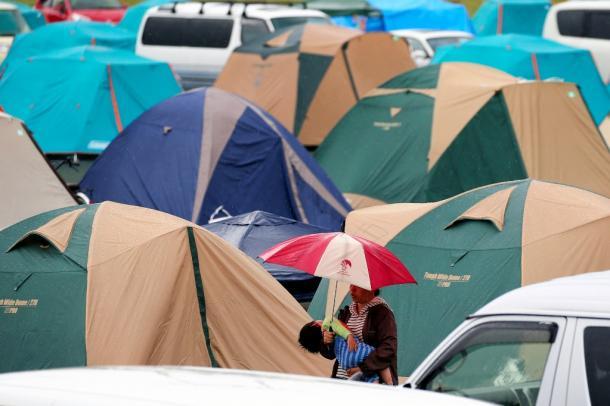 テントが並ぶ避難所で、傘をさして子どもをあやす母親=5月3日、熊本県益城町