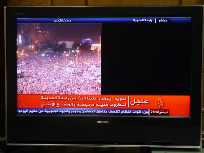 写真・図版 : エジプトのクーデター直後、カイロ市内の反ムルシデモとムルシ支持デモを画面を半分に分けて映していたテレビが、反ムルシデモの映像だけになった=2013年7月4日