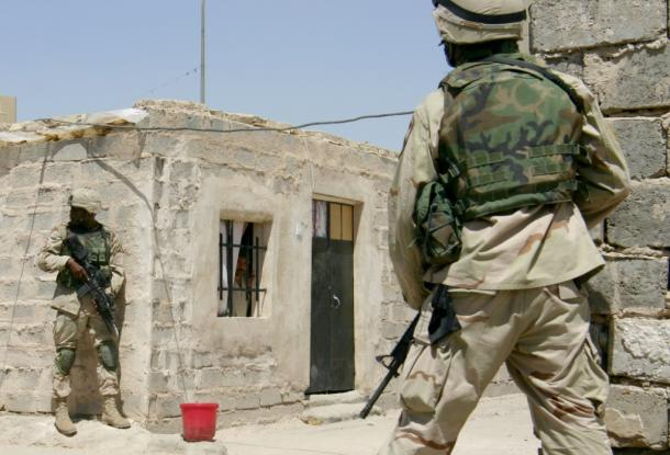 バグダッド市内で掃討作戦を行う米兵たちと、建物内でおびえながら外の様子をうかがうイラク人男性=2004年7月、志葉玲撮影