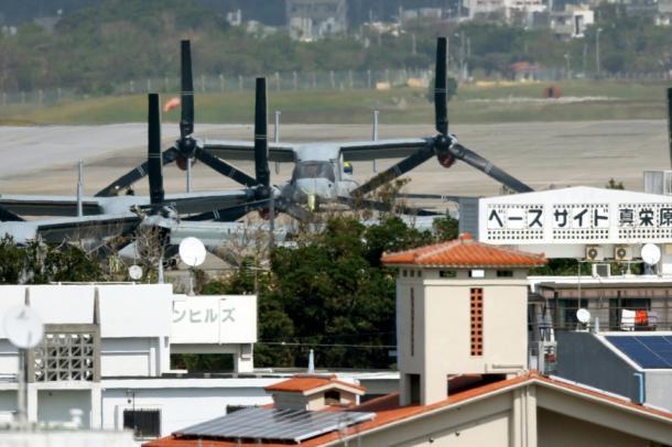 米軍普天間飛行場の周囲には住宅などが立ち並ぶ。建物の向こうに、駐機するオスプレイ2014