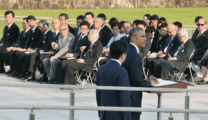 写真・図版 : 原爆死没者慰霊碑への献花を終え、演説するオバマ米大統領(手前右)の言葉を聞く被爆者ら=5月27日午後5時43分、広島市中区の平和記念公園、代表撮影