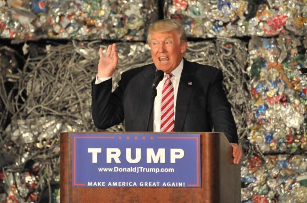 経済政策について演説する共和党のトランプ氏。背後には、圧縮されたアルミ缶のブロックが積み上がっていた=2016年6月28日、米国ペンシルベニア州モネッセン、金成隆一撮影