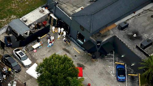 写真・図版 : 米フロリダ州オーランドで銃乱射事件があった現場を調べる捜査員ら=ロイター