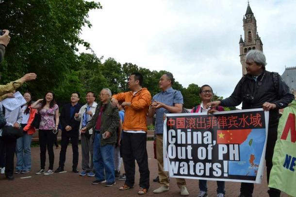 写真・図版 : オランダ・ハーグの仲裁裁判所がある平和宮前でデモをする中国人とフィリピン人たち=2016年7月12日