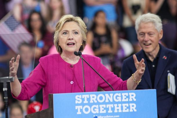 民主党の大統領候補の指名を受諾後、最初の集会で演説するクリントン前国務長官(左)。夫のビル・クリントン元大統領が見守った=7月29日、フィラデルフィア、ランハム祐子撮影