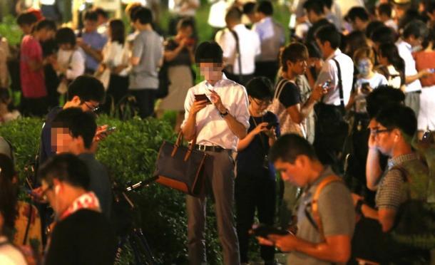 スマホ片手に扇町公園に集まった人たち=29日午後8時12分、大阪市北区