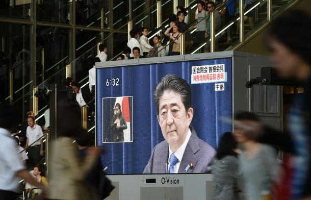 写真・図版 : 消費税増税再延期を表明する安倍首相を映し出す大型ビジョン=6月1日、大阪市北区