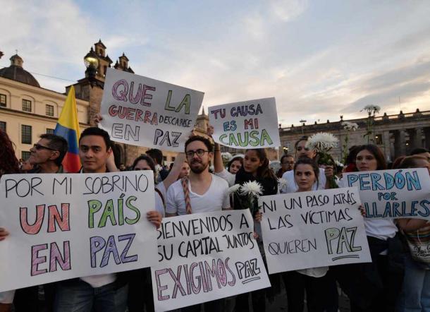 写真・図版 : コロンビアの首都ボゴタの広場で、「犠牲者は平和を望む」などと書かれた紙を掲げ、内戦終結を求める人たち=2016年10月12日