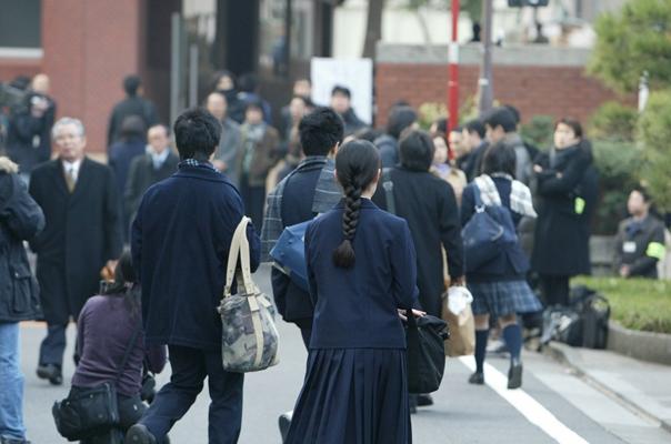 都立高の入試会場では、門前で学習塾の講師らが見送る中で、受験生が校舎へと入っていった=2006年、東京都千代田区