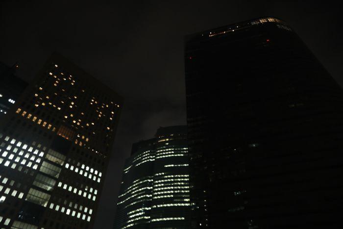 写真・図版 : 午後10時すぎに一斉に消灯された電通本社ビル(右)=東京都港区