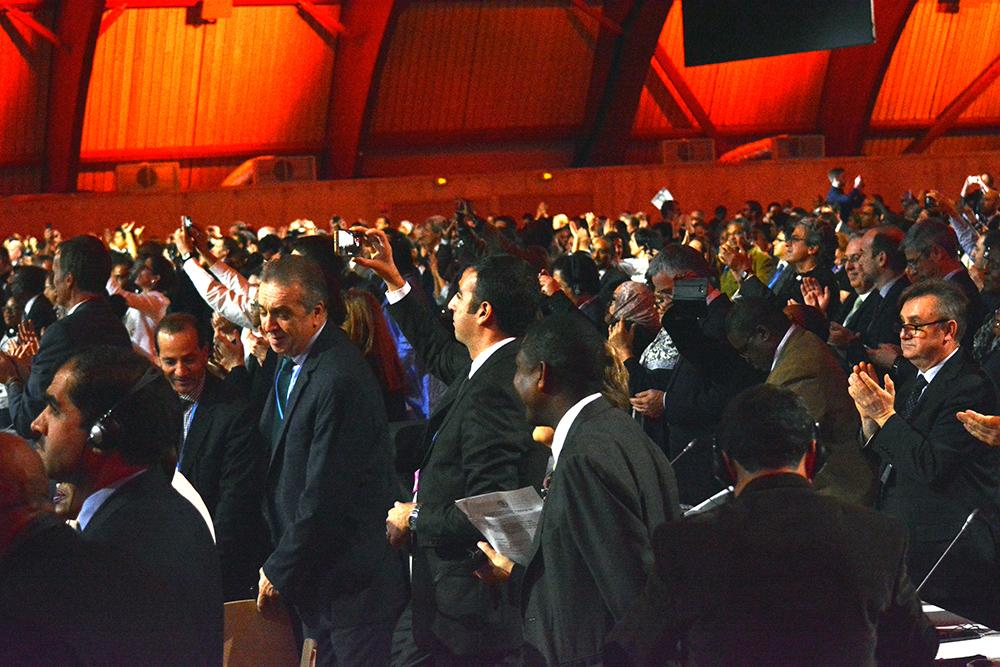 パリ協定の採択を喜ぶ参加者たち=2015年12月、パリ近郊、下司佳代子撮影