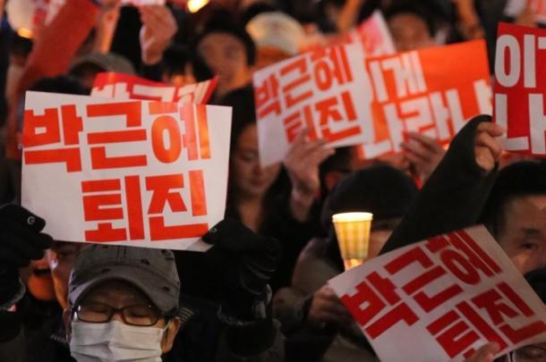 ソウル市内の中心部で開かれた集会で、「朴槿恵退陣」と書かれたプラカードを掲げる参加者たち=10月29日