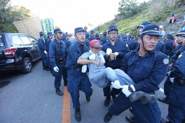 ヘリパッド移設工事再開に抗議し座り込む人たちを排除する機動隊員ら=22日午前7時すぎ、沖縄県東村高江20160722