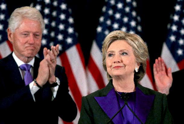 ニューヨークで9日、敗北宣言をした会場で拍手を受けるヒラリー・クリントン前国務長官(右)。夫のビル氏が付き添った=ロイター