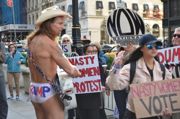 ニューヨークのトランプタワー前で抗議活動をする女性たちと、NYに出没するトランプ支持の「「ネーキッドカウボーイ」