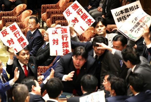 衆院TPP特別委で、採決に反対する野党議員らが詰め寄る委員長席を見る山本有二農水相(左奥)20161104