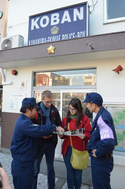 外国人観光客の相談に応じる警察官。左腕には英語が出来ることを示す大きな腕章を付けている=JR鎌倉駅前