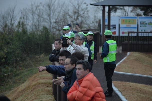 津波警報が出たため、高台に避難した人たち。心配そうに海岸を見つめていた=22日午前6時26分、福島県楢葉町20161122