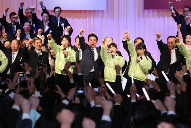 自民党大会で10代の党員らとともにガンバロー三唱で拳を突き上げる安倍晋三総裁(中央)=3月13日