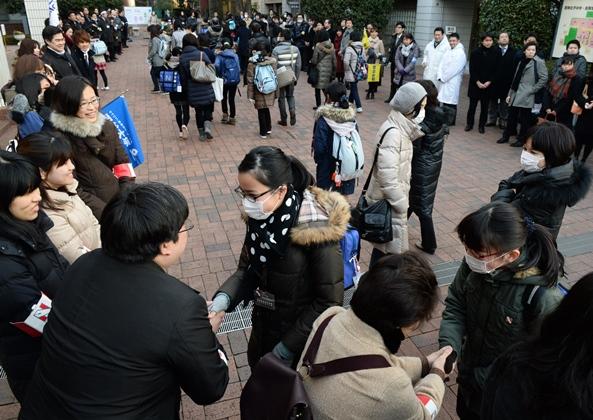 塾関係者らが激励するなか、入試会場に続々と入る受験生=2016年2月1日、東京都武蔵野市の吉祥女子中学校