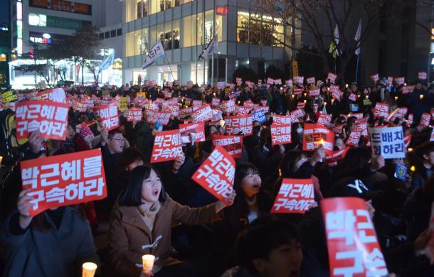 韓国・大邱市で10日、「朴槿恵を拘束しろ」と書いた紙を掲げる集会の参加者たち20161210