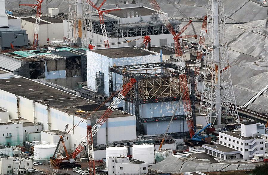 写真・図版 : カバーが外され、大破した建屋が見える福島第一原発1号機=12月10日