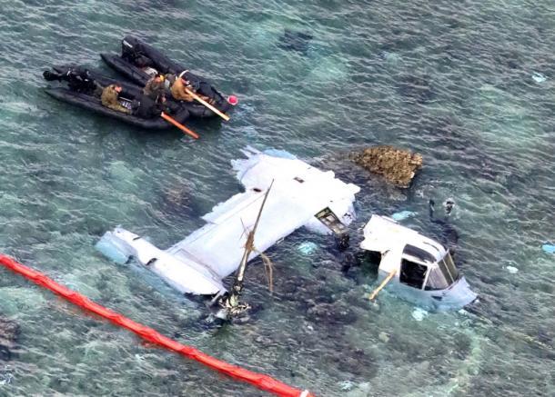 ボートに乗った米軍関係者が大破したオスプレイの機体を調べていた=15日午前11時31分、沖縄県名護市安部20161215