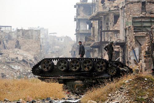シリアのアレッポで13日、破壊された装甲車両の上に立つアサド政権軍の兵士=ロイター