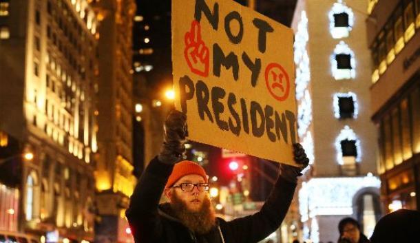 大勢の人々が足早に行き交うニューヨーク5番街。トランプ氏の住居があるトランプタワー前で、「私の大統領ではない」と書いたボードを掲げた男性が静かに立っていた=2016年12月