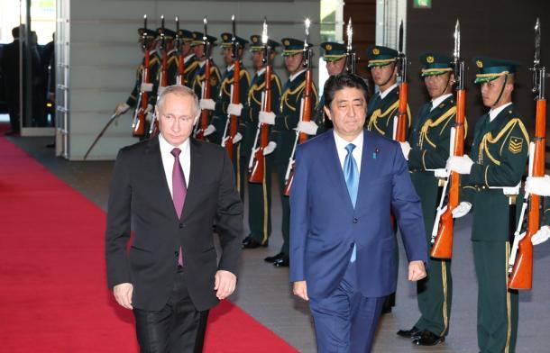 儀仗(ぎじょう)隊が並ぶ中、安倍晋三首相(右)の出迎えを受け、官邸に入るロシアのプーチン大統領=16日