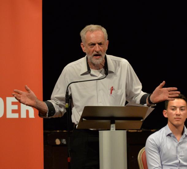 写真・図版 : ワイシャツの胸ポケットにペンを挿したラフないでたちで演説する英労働党の党首候補ジェレミー・コービン氏=2015年8月、ロンドン西部イーリング