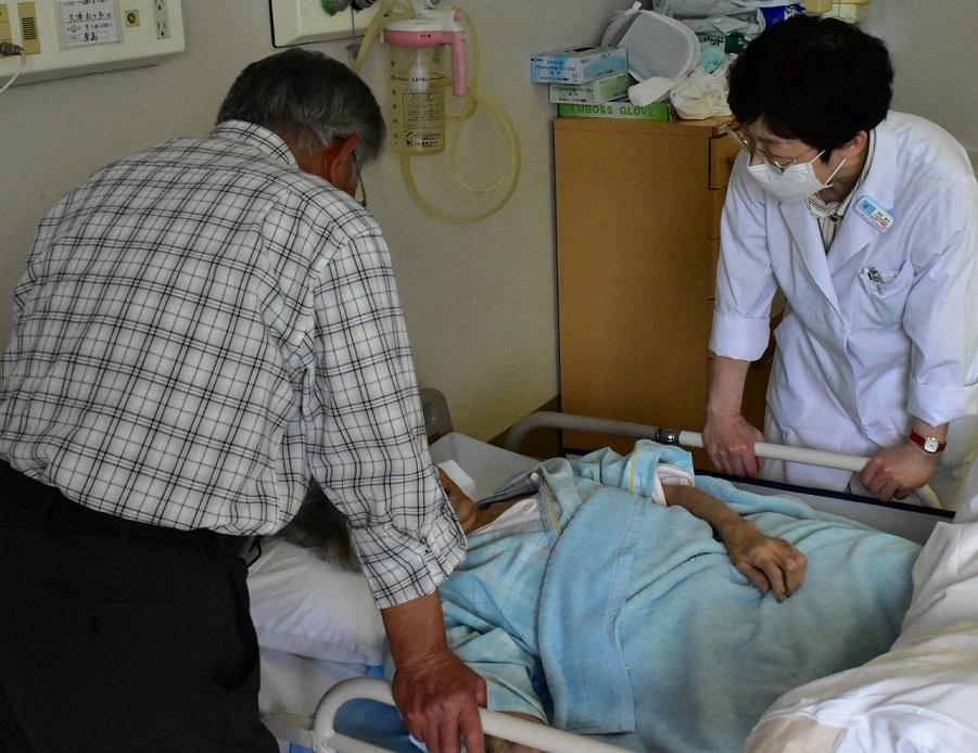 写真・図版 : イタイイタイ病の患者認定を求めている女性を見舞う家族(左)と医師