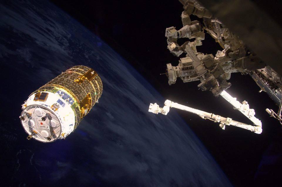 写真・図版 : 国際宇宙ステーションのロボットアームでキャプチャーされる日本の無人補給船「こうのとり」(NASA/ESA/JAXA)