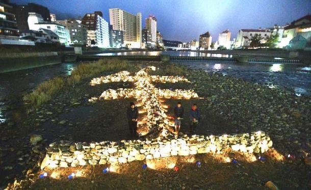 阪神・淡路大震災の発生時刻の12時間前に「生」の文字のそばで黙祷(もくとう)する人たち=16日午後5時46分、兵庫県宝塚市