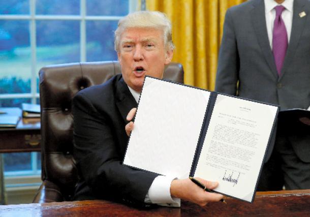 TPP離脱の大統領令に署名したトランプ新大統領=ロイター