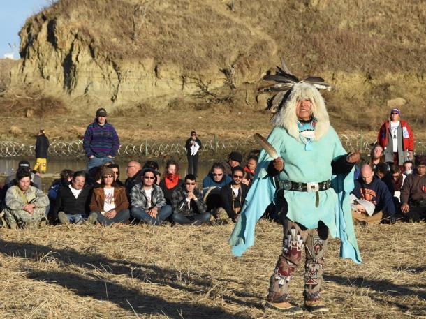 パイプラインの建設予定地の近くで11月26日、ネイティブアメリカンの祈りを聞く抗議者。川の向こうには鉄条網が張られている=米ノースダコタ州キャノンボール付近