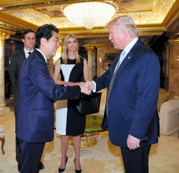 大統領就任が決まったトランプ氏(右)と会談し、握手する安倍晋三首相。後方は長女のイバンカ氏夫妻=2016年11月、米ニューヨーク、内閣広報室提供