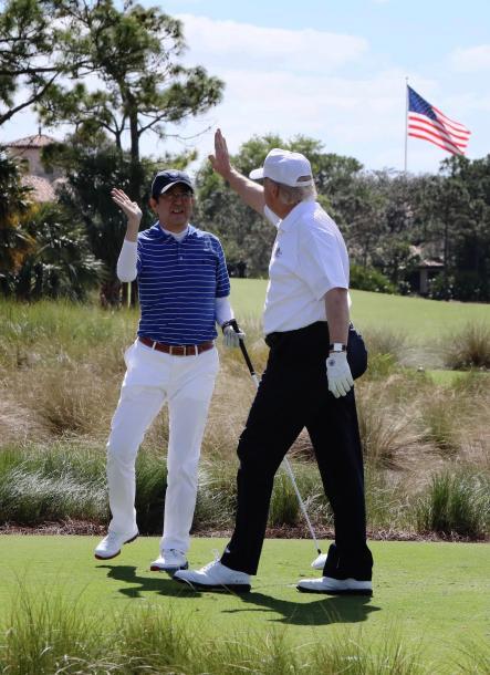 米フロリダ州・パームビーチでゴルフを楽しみ、ハイタッチをする安倍晋三首相(左)とトランプ大統領=2月11日、内閣広報室提供