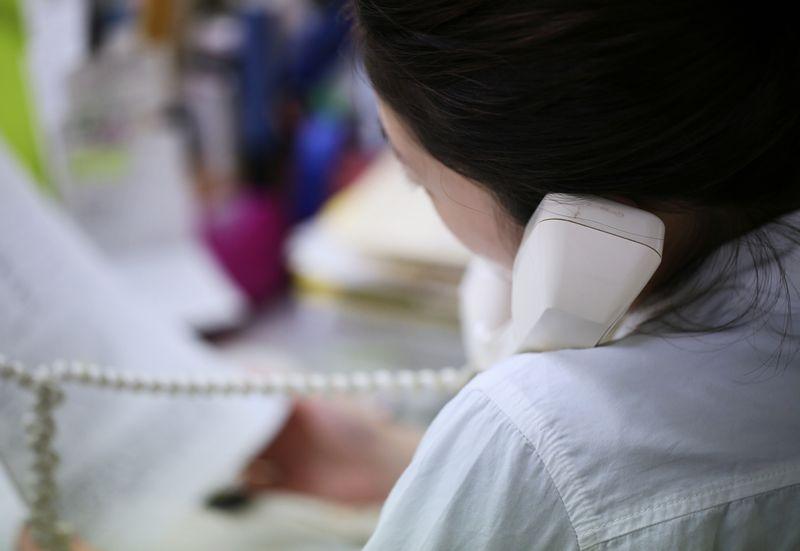 写真・図版 : 資料をめくりながら保護者と話をする児童福祉司